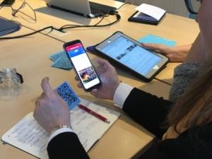 Mit ihrem Handy und einem QR-Code versucht eine Teilnehmerin des Digital Summit das Rätsel bei BreakoutEdu zu lösen.