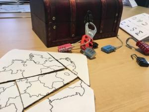 Eine Übung bei BreakoutEdu: Eine Deutschlandkarte als Puzzle liegt vor der immer noch verschlossenen Schatztruhe