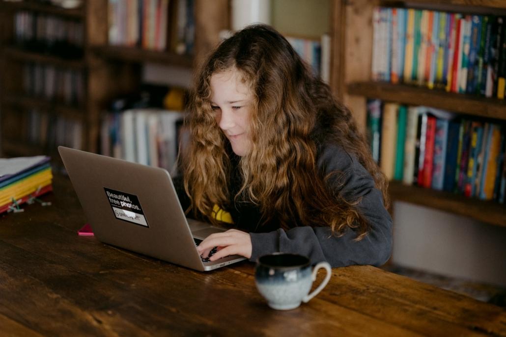 Ein Mädchen sitzt zu Hause vor einem Laptop und arbeitet.