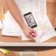 Schüler arbeitet am Bildschirm und recherchiert am Handy