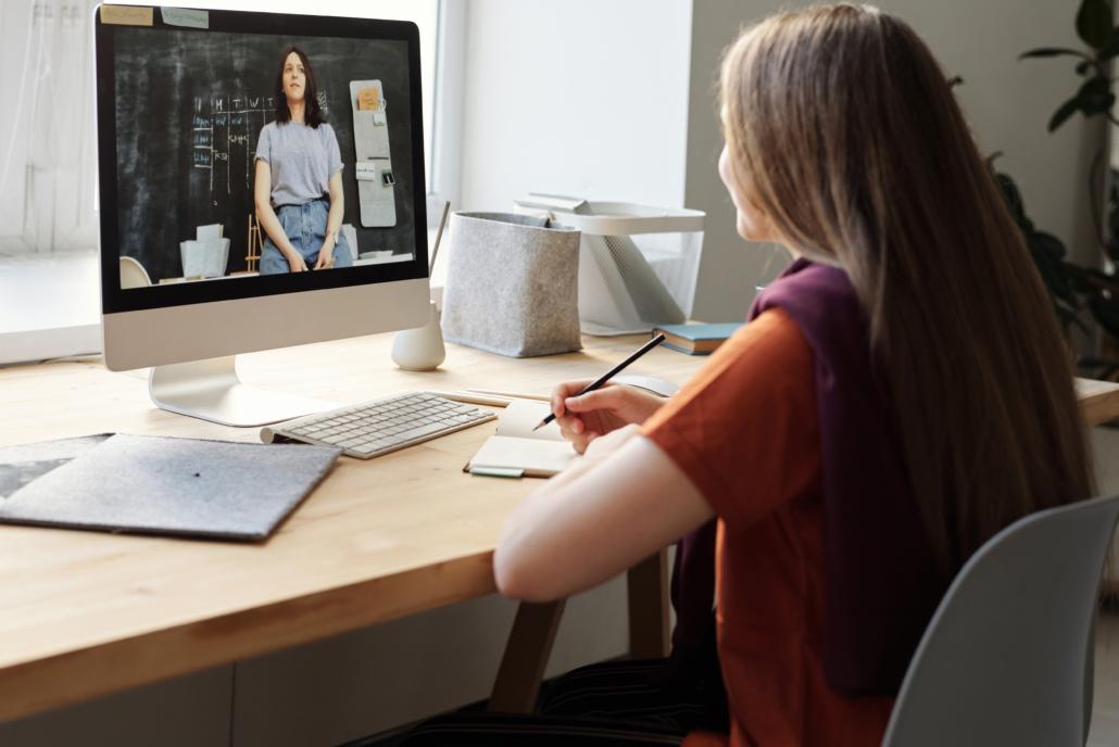 Kind sitzt mit Noitzblock am PC und schaut ein Video von einer Frau in der Schule