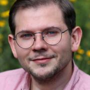 Porträt von Dozent Thomas Odemer, Mann mit Brille und braunen Haaren in rosa Hemd, im Hintergrund Blumenwiese