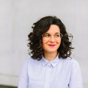 Porträt Vasiliki Mitropoulou, Frau mit Locken und Brille in Bluse