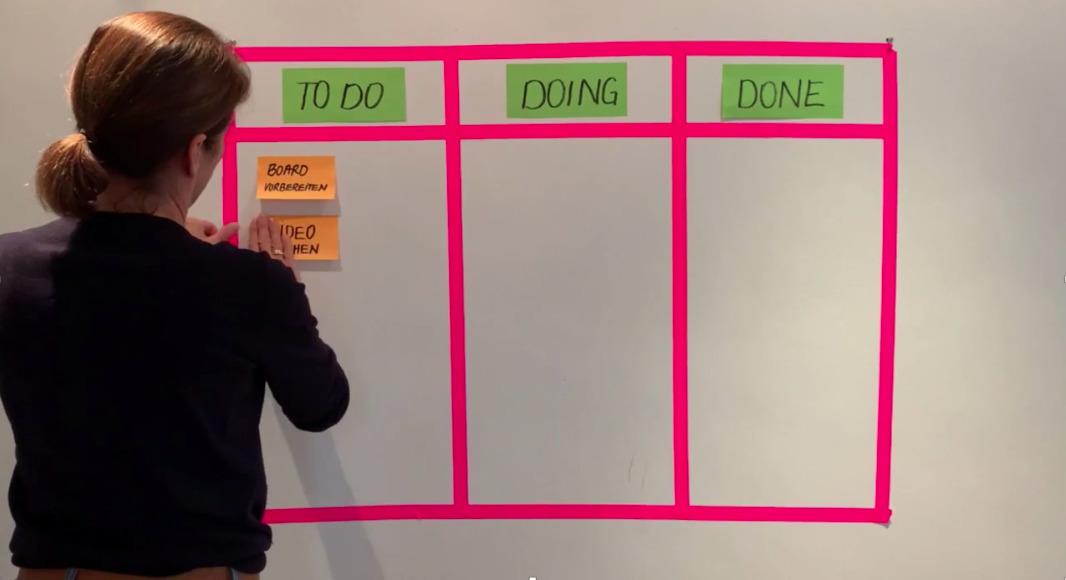 Foto zeigt eine Frau von hinten während sie ein analoges Kanban-Board an der Wand mit farbigem Klebeband und Klebezetteln erstellt