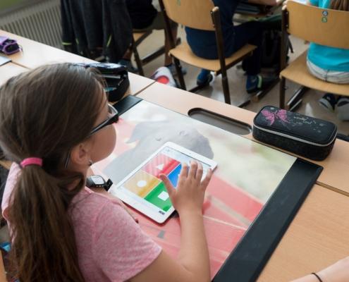 Ein Kind sitzt am Schultisch und hat ein Tablet vor sich liegen.
