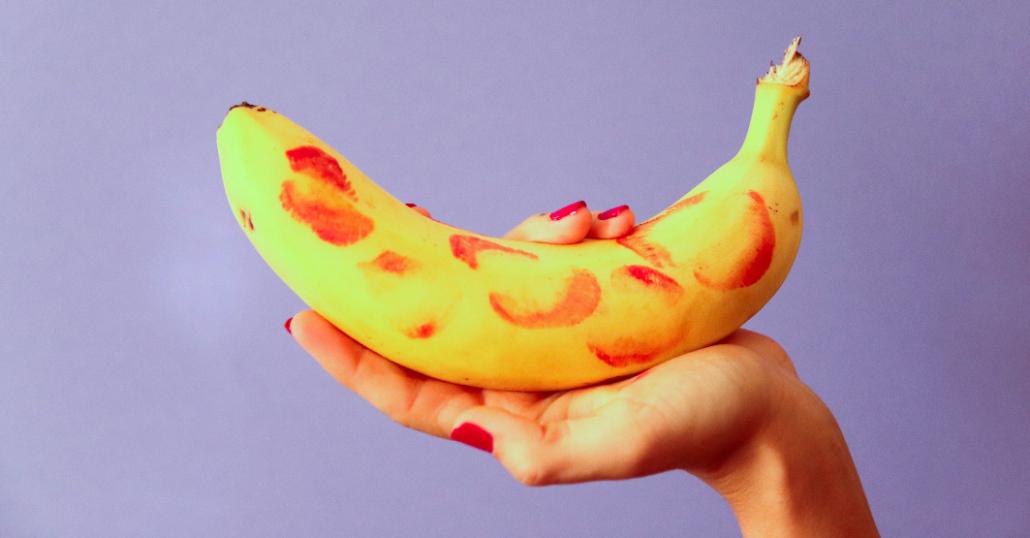Hand mit rotem Nagellack hält eine Banane, auf der Abdrücke von Lippenstiftküssen zu sehen sind