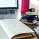 Ein Kalender, ein Smartphone, ein Laptop und eine Tasse Kaffee stehen auf einem Holztisch.