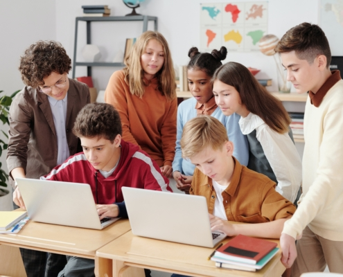 Kinder stehen um Computer in der Schule